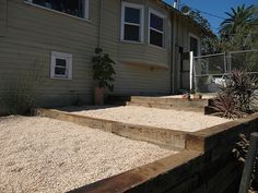 terraced backyard with railroad ties and gravel