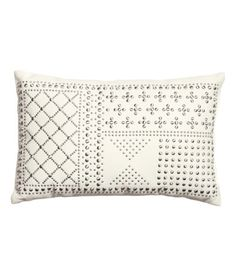 Cushion with Studs $24.95 Cushion in cotton twill with metal studs at front. Polyster fill. Size 8 3/4 x 13 3/4 in. 100% cotton. Machine wash cold Imported