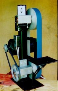 Belt Grinder Homemade belt grinder constructed from custom-cast aluminum contact wheels, bearings, tubing, steel plate, switch, pulleys, and an electric motor
