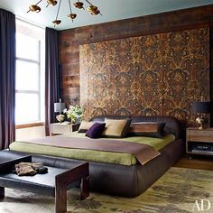 A 19th-century gilded-leather screen from Dmitriy & Co. spans one of the bedroom walls; the 1970s chandelier is from Lucca Antiques, the bed is from Siglo Moderno, the table lamps are by Kriest, the green silk coverlet is by Frette, and the carpet is from Doris Leslie Blau.