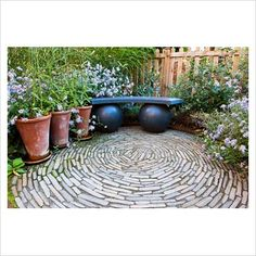 GAP Photos - Garden & Plant Picture Library - Paved circular patio with modern bench - GAP Photos - Specialising in horticultural photography