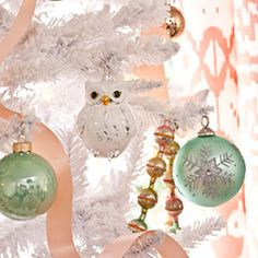 #Dress_Up_Your_Tree - Use candy-colored ornaments and garlands that look like #jewelry for a glitzy look. Simple round ornaments in glossy peach and aqua stand out just enough from the white branches and the metallic beaded garland coordinates with all the other #sherbet_shades in the room.