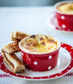 Alyn Williams adds a few simple twists to a classic breakfast dish with this baked eggs recipe. Smothering the eggs in a thick cheese sauce, and adding a savoury Marmite hit to the toasted soldiers, turns it into a fun breakfast, brunch or even an afternoon snack dish.