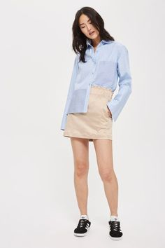 The mini skirt goes casual in this super basic style. In a neutral nude, it comes in a paperbag shape. We've styled with a crisp shirt for a smart update.