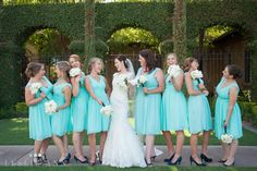 A candid photo of the bride and her bridesmaids. Tiffany blue, v-neck, knee length dresses with white bouquets   Leslie Ann Photography   villasiena.cc