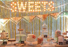 Fringe sweets table at a modern-meets-vintage wedding reception in a rustic barn. The dessert table pops with charming bunting, streamers, homemade marquee lighting, vintage cake stands, pretty cakes and confections.