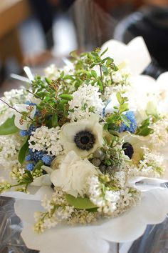 Spring bouquet of white lilac, panda anemones, blue muscari, sweet peas, and silver brunia