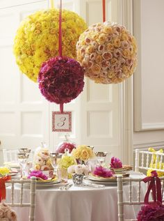 Three giant, brightly coloured pomanders suspended from the ceiling as wedding decorations. // Philippa Craddock Flowers.