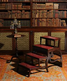 Facing a library filled with antique books having gilded bindings, a tripod kettle table and a Regency mahogany metamorphic library armchair, circa 1815, following a design by Morgan & Sanders, with bar back and scrolled arms above sabre legs, with brass catch securing hinged action becoming a flight of four library steps - Dim of metamorphic chair: As a chair 91cm high, 55cm wide, 58cm deep - As steps 73cm high, 55cm wide, 105cm deep