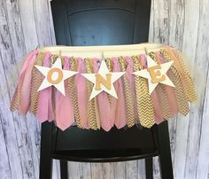 This adorable highchair tutu will be perfect for your babys birthday party or photo shoot! It is made with pink fabric, gold chevron fabric, white tulle and gold tulle along with white stars and gold letters! The hearts are held up with tiny clothespins that are attached to natural twine. This measures 30 wide with 20 of fabric strips and 5 of twine on either side of the strips. The fabric strips measure about 8-8.5 long. If you need this larger just let me know! I can customize this with…