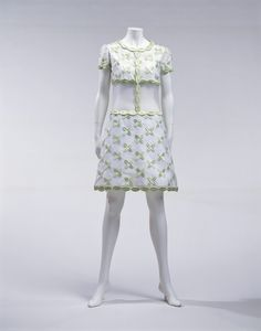 DressAutumn/Winter 1967  Designer:   André Courrèges  Brand:   André Courrèges  Label:   COURRÈGES PARIS  Material:   White cotton satin layered with silk organdy with light green floral embroidery; silk organdy at waist.