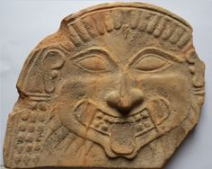 Greek antefix, Tarantine terracotta antefix, late 6th century B.C. Semi circular in form, molded with a Horgoneion, the wide face with large Almond shaped eyes and a prominent nose, the tongue protruding through fanged teeth, with a pronounced chin, the beard with pointed locks, stylized hair across the forehead, three rows of braids framing the face, 20 cm high. Private collection