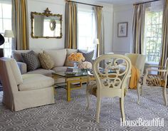 To break up the monotony of the color gray in the living room of this Brookville, New York home, interior designer Andrew Raquet used silver, gold, and lots of pattern.    - HouseBeautiful.com
