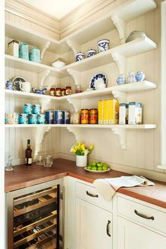 A butler's pantry, just off the kitchen, with bracketed shelves on beadboard walls put items on display. | Photo: Anthony Tieuli | thisoldhouse.com