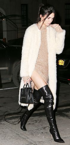 Kendall Jenner wearing a Ashley B Long Faux Fur Coat, Celine dress and bag and Alice + Olivia Dae over-the-knee boots