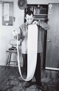 Jack Kerouac displaying scroll containing his book, On the Road, 1964