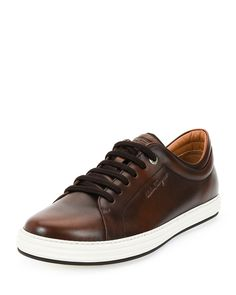"Salvatore Ferragamo ""Newport"" low-top sneaker in calfskin leather. Round toe. Lace-up front. Embossed logo at sides and tongue. Padded collar. Leather lining and insole. Contrast rubber outsole. Made"