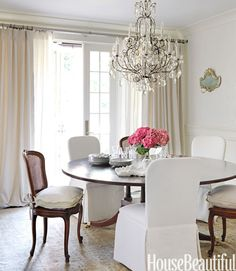 In bright pink, hydrangeas add a burst of color to a shades-of-white dining room in an Alabama home by Tracery Interiors. The beaded-crystal chandelier is antique. The walls are painted China White by Benjamin Moore.   - HouseBeautiful.com