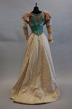 Brocaded satin evening gown with elaborately sequined and beaded bodice, and with turquoise velvet cummerbund and trim (back), c. 1900.
