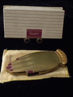 Volupte's 'Golden Gesture' compact with ruby fingernails, dust cover, orig. box, 1946.