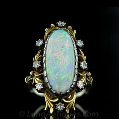 A gorgeous antique opal ring from the first decade of the twentieth century is finely crafted in two-tone white and yellow gold flourished w...