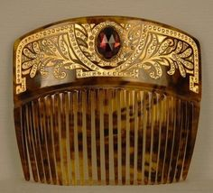 PIQUE D'OR HAIR COMB, c. 1900. Curved faux tortoise back comb with gold foliate design having paste insets and mounted with a large faceted amethyst cabochon.