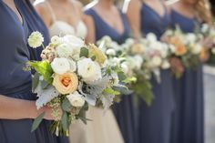 bridesmaids in lovely french blue gowns carry their loosley tied and organic bridesmaid bouquets of white patience garden rose, white ranunculus, vendela rose, white majolik spray rose, white scabiosa, dusty miller, fern, seeded eucalyptus, mondial rose, light peach rose & peach stock wrapped in cream satin ribbon.