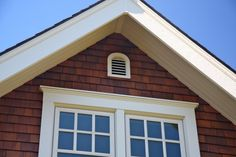 Tongue-and-groove soffit, Type I cedar shingles (finished with Sikkens Cetol Log & Siding 078 Natural), and wood gable vent; wood windows and trim.
