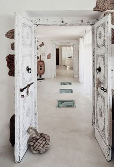 #Sardinia, Italy. The interior is designed by Marina Wenger from Geneva. Most furniture pieces and accessories come from Asia: doors from Indian and other Indian and Chinese pieces create a warm and rustic look throughout the house.