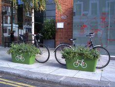 Boa alternativa            Uma ideia simples e que pode transformar um estacionamento de bicicletas em pequenos jardins comunitários. Vasos de flores e ervas espalhados pela cidade que funcionam como porta - bicicletas. Acha que nao é seguro? Não substime o poder de um ramalhete de alecrim, ele pode distrair pessoas mal intencionadas e assim, sua magrela ficará protegida.