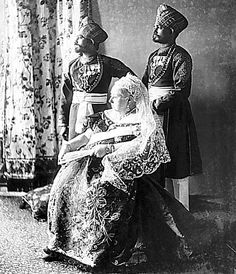 Photograph of Queen Victoria seated with her two Indian servants Mustafa (fl. and Chidda (fl. standing behind her in full uniform with medals. The Queen is holding a fan in her left hand.This photograph was issued during the Diamond Jubilee year of Queen Victoria Family, Queen Victoria Prince Albert, Victoria Reign, Victoria And Albert, Victoria S, Royal Queen, King Queen, Elizabeth Ii, Reine Victoria