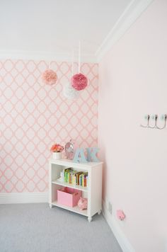 Jazz up the corner of your nursery with a fun, styled bookshelf and some fabric pompoms hanging from the ceiling!