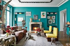 Vivid turquoise walls encase fashion designer Stefano Pilati's Paris living room, where his white boxer, Pepi, reclines on a carpet from Nilufar. The ceiling fixture is composed of Charlotte Perriand sconces, and the art includes works by Giorgio di Chirico, Henry Moore, Rosemarie Trockel, and Sonia Delaunay.