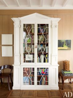 In an oak-paneled New York living room stands a late-19th-century painted bookcase by the English architect Alfred Waterhouse.  DESIGNER: Len Morgan PHOTOGRAPHER: Joshua McHugh