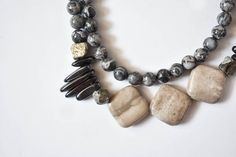 This Designs by s.e.K long silver lace agate necklace features pyrite, grey marble, and hematite stones with an asymmetrical style and an antique brass button clasp. This necklace can be worn long or doubled for a statement look.