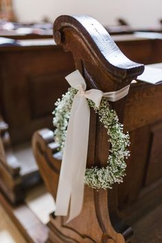 Dekoration für die Trauung in der Kirche mit einem Kranz aus Schleierkraut an der Kirchenbank. Foto: Jung und Wild Design