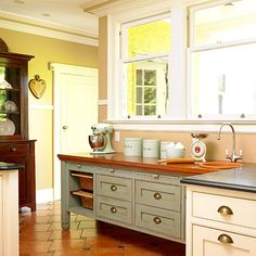 An easy way to designate a baking center in the kitchen and give it special attention is to finish the cabinetry differently from the rest of the room. This large baking center has a fresh country look while offering abundant storage and work space. The extra room is great when there are helpers in the kitchen. The small sink is perfect for cleanup.