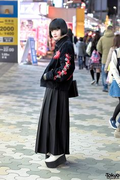 21-year-old Japanese architect Kurumi on the street in Harajuku wearing a Tailor Toyo souvenir jacket with a Comme Des Garcons pleated maxi skirt, Murua platforms, and a Moussy box purse.