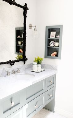 Bathroom with white walls, light blue cabinets, marble counter top, glass and silver light fixture, and grey tile floors