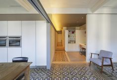 I decori in gesso sul soffitto sono stati recuperati e ristrutturati, così come le piastrelle in ceramica del pavimento nell'appartamento catalano The VVall di Nook Architects. La cucina è stata disegnata su misura in total white. La poltroncina è il modello con struttura in betulla Ekenäset di Ikea