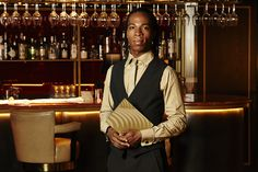 Quaglino's wonderful waiter ready to serve, menu in hand. His Studio 104 uniform is tailoring at its finest.