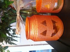 """Pumpkin candle holders. Clear wax out of old candle holders. Cut face shapes out of duct tape. Spray two coats of orange spray paint, let dry. Spray two coats of """"orange blast"""" glitter blast spray paint. Peel off duct tape pieces. Boom, homemade Halloween decorations!"""