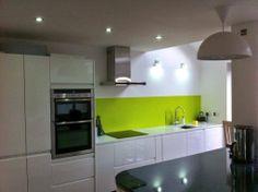 Wren Living: White Handleless Gloss Kitchen with a specialist Super White quartz worktop! The green splashback is so refreshing.