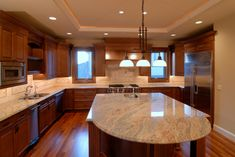 A gorgeous kitchen with a bold contrast of light marble countertops and dark cherry cabinetry.