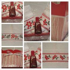Maceta rectangular en tono rojo con craquelado blanco, dos toallas de mano con bordados en punto cruz de flores en tono rojo.