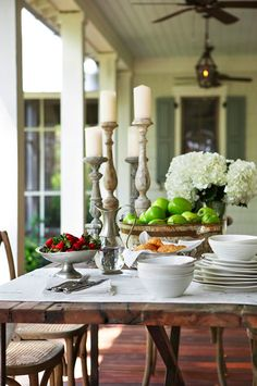 Open porch with rustic table. Love the big bowl of green apples with the tall candles and white flowers. Very chic.