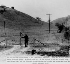 """Leffingwell Homestead and property located on Long Valley Road, September 1951. Caption reads: """"The old building on the right is the Leffingwell Homestead. There was a local rumor that gold was buried under the house. We never found it. On the skyline is the No. 1 water tank. The car is on Long Valley Road, and the wire gate is the center line of what was to become Round Meadow Road."""" Calabasas Historical Society. San Fernando Valley History Digital Library."""