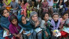 Young schoolgirls receive new notebooks and textbooks at a refugee camp in Muzaffarabad, Pakistan. Many girls in Pakistan still don't receive an education.