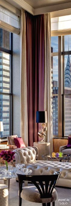 Glam living room with tall layered draperies with simple wood cornice to hide the hardware.  And the view... of the top of the Chrysler building.