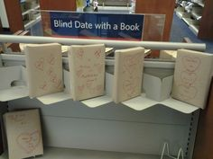 """Another version of Blind Date with a book from a library: """"My local library branch started doing this """"Blind Date with a Book"""" thing, thought you guys might like it.The shelf was full when we got there, but was like this as we were leaving. The books are wrapped in paper and have different designs on them, and then a few words vaguely describing the subject matter of the book. Things like """"Drama"""", """"Plot Twists"""", """"espionage"""", etc. libraries, books, dates, shelves, dramas, thought, papers, design, branches"""
